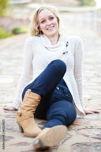 canvas print picture Smiling young blonde woman relaxing on pavement