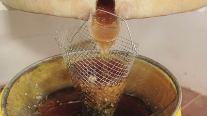 Honey spinner extracting raw honey, medium shot