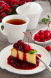 A slice of cheesecake with cherry sauce.