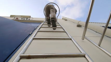 Worker on the ladder in industrial plant