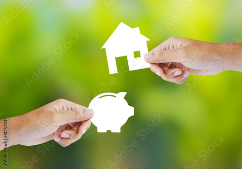 Hand holding paper piggy bank and house shape. Banking concept