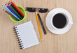 Notebook, cup of coffee and colorful pencils on wooden table