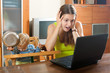 Sorehead mother with baby using laptop