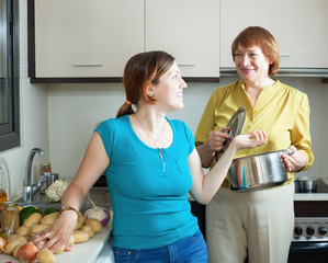 Mature woman and adult daughter  in kitchen
