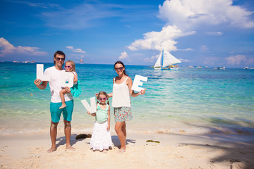 Young happy family on tropical vacation with word LOVE