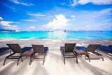 Beach chairs on exotic tropical white sandy beach