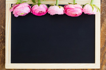 Pink ranunculus on a black frame