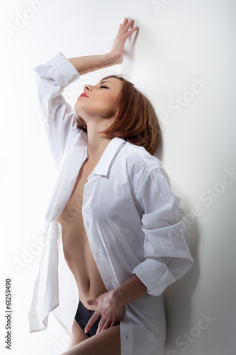 Excited redhead girl posing leaning against wall