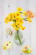 Bouquet of yellow lent lilly (daffodil) with easter eggs on a wo