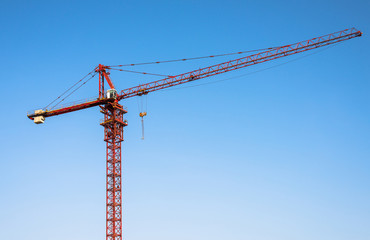 Red tower crane on blue sky background.