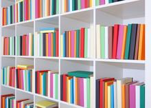 Bücher auf einem weißen Regal, Stapel von bunten Bücher in der Bibliothek