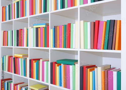 Books on a white shelf, stack of colorful books in Library