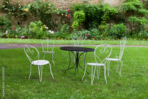 The empty table and four white chairs in the garden