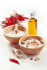 Rice in wooden bowl with ingredients for risotto