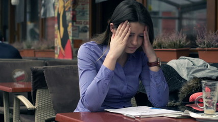 Overwhelmed pretty businesswoman with documents sitting in cafe