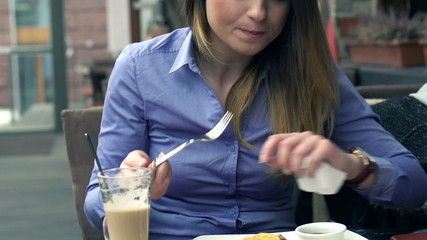 Beautiful businesswoman eating tasty pancakes in cafe