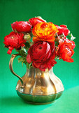 ranunculus flowers in a metal jug on a green background .