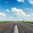 asphalt road close up under clouds in blue sky