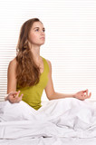 Beautiful girl meditating in bed