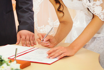 Bride signing marriage license or wedding contract