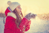 Beauty Winter Girl Blowing Snow in frosty winter Park. Outdoors
