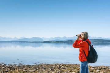 Woman tourist looking through binoculars