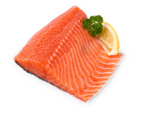 Raw, red salmon fillet with lemon wedge