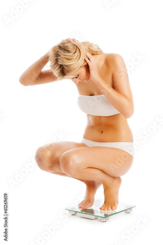 Sports Woman Crouching on Bathroom Scales.