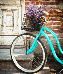 Vintage bycycle with basket with lavender flowers near the woode