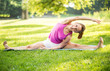 Cute young woman doing stretching exercises in the park.