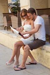 Junges Paar auf Reisen: Lesen eines Reiseführers