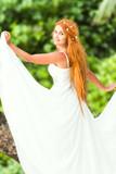young beautiful woman in bridal wedding dress on natural backgro