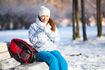 Young woman with backpack heating hands in mittens, copyspace