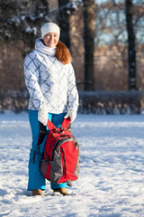 Young Caucasian woman standing with backpack in winter park