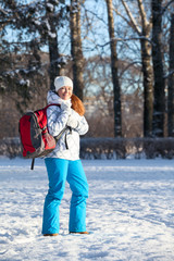 Young Caucasian woman walking with backpack in winter park