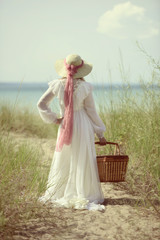 summertime woman at the beach with picnic basket