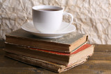Cup of hot tea on books on table on paper background