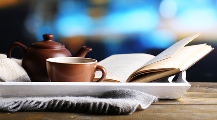 Cup of hot tea with teapot and book