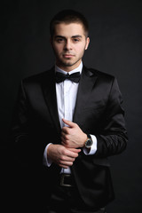Handsome young man in suit on dark background