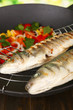 Delicious grilled fish on wok close-up