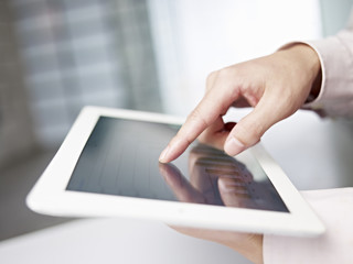 finger touching screen of tablet computer