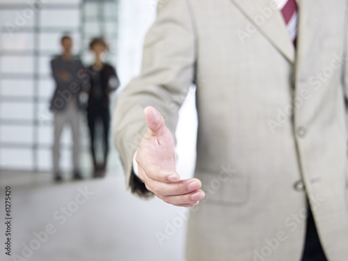 businessman reaching out for a handshake