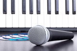 Microphone, cd disks and piano keyboard on black table