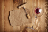 Red wine glass, corkscrew and paper for your note