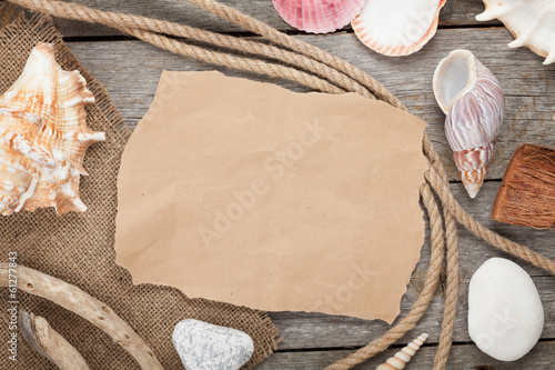 Old paper with rope and seashells on wooden textured background