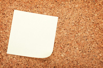 Blank postit note on cork wood notice board