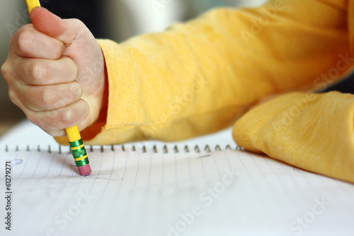 Child's Hand Erasing with Pencil on Notebook Paper