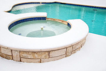 Outdoor hot tub or spa by swimming pool in the winter