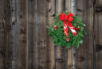 Holiday wreath hanging on rustic wooden fence