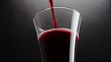 Cherry juice in glass on black background